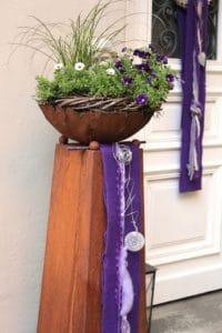 Metallsaeule mit lila Wollvlies dekoriert